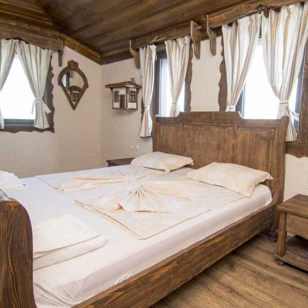 Двойна стая с дървено легло и тераса.