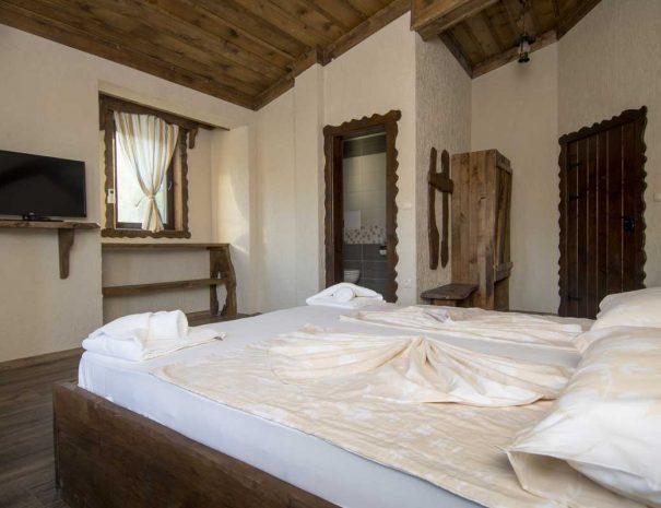 Хотелска стая с обзавеждане от дървени мебели.