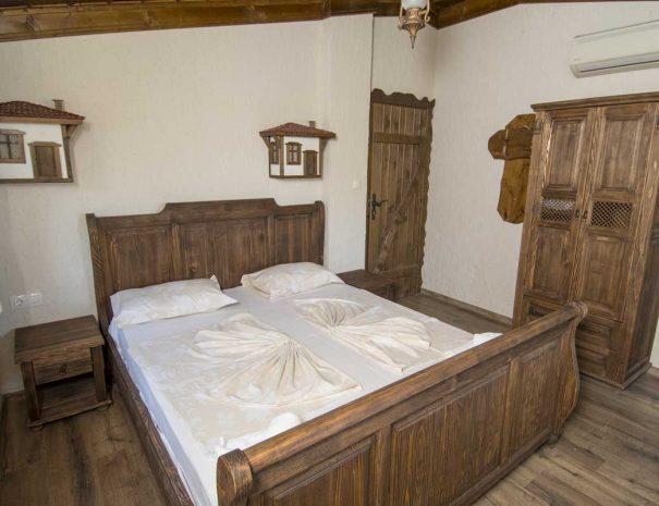 Дървено двуместно легло и дървен гардетоб в стая.