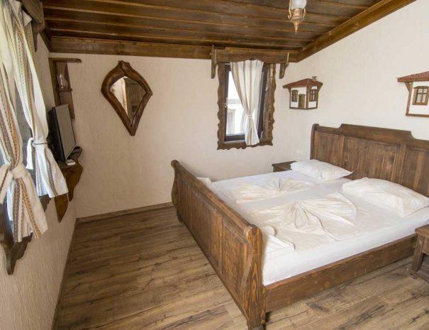 Дървена спалня в стая с прозорци и огледало.