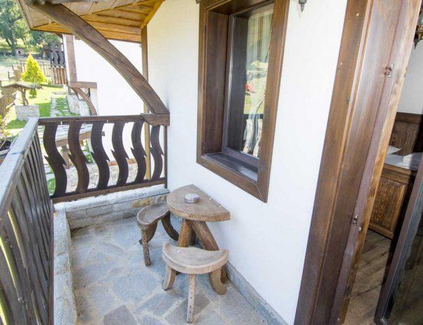 Тераса с дървени маса и столове.