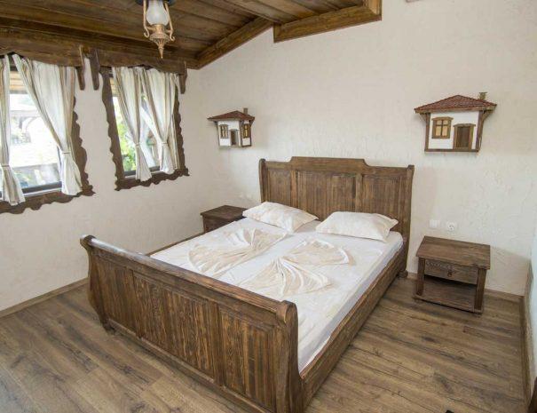 Спалня с дървено двуместно легло.
